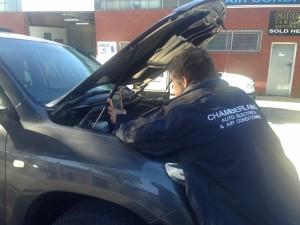 vehicle electrician at work under bonnet